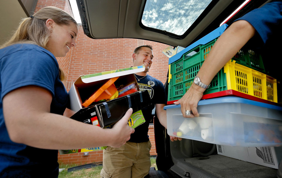 Photo - University of Central Oklahoma students Kaelin Fink and Rance Rue unload toys from a truck as UCO students, faculty and staff deliver books, balls, art materials and other child development items on Thursday, July 11, 2013 in Yukon, Okla. to the  South Yukon Church of Christ. The church is where the he Canadian Valley Technology Center  Child Development Center has relocated to after being severely  damaged by the May 31 tornadoes that hit El Reno.    Photo by Chris Landsberger, The Oklahoman