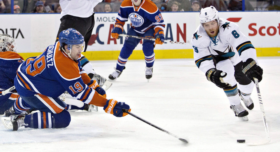 Photo - San Jose Sharks Joe Pavelski (8) and Edmonton Oilers Justin Schultz (19) reach for the loose puck during the first period of an NHL hockey game in Edmonton, Alberta, on Wednesday, Jan. 29, 2014. (AP Photo/The Canadian Press, Jason Franson)