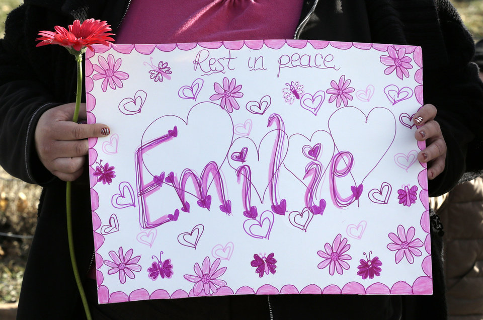 Photo - A mourner holds a sign after a hearse carrying Emilie Parker drove by following funeral services for Emilie on Saturday, Dec. 22, 2012, in Ogden, Utah. Emilie, whose family has Ogden roots, was one of 20 children and six adult victims killed in a Dec. 14 mass shooting at Sandy Hook Elementary in Newtown, Conn. (AP Photo/Rick Bowmer) ORG XMIT: UTRB114