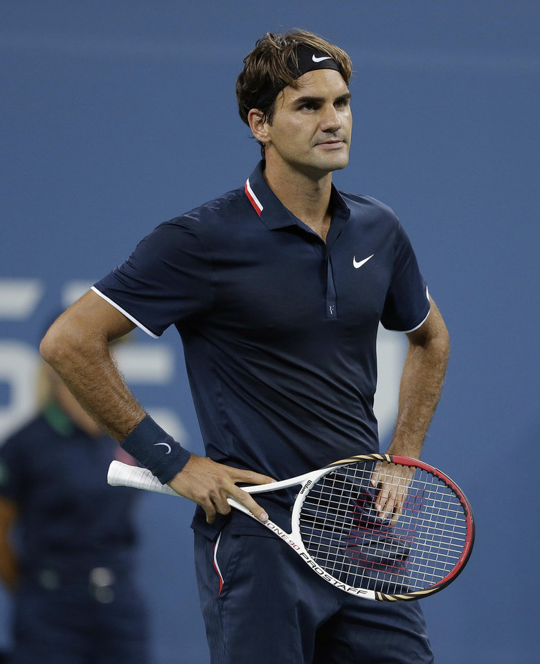 Photo -   Roger Federer, of Switzerland, watches a replay during a quarterfinals match against Tomas Berdych, of the Czech Republic, at the U.S. Open tennis tournament on Wednesday, Sept. 5, 2012, in New York. Berdych won 7-6 (1), 6-4, 3-6, 6-3. (AP Photo/Darron Cummings)