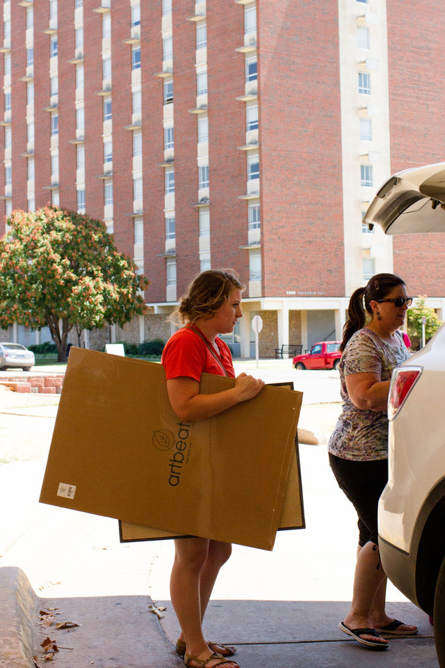 Photo - Amy Higdon, left, and her mother, Danna Higdon, unload their car in front of a  residence hall at Oklahoma State University. Students moved into the OSU dorms Monday in Stillwater. Photos by Mitchell Alcala for the Oklahoman  Mitchell Alcala - Mitchell Alcala for the Oklahoma