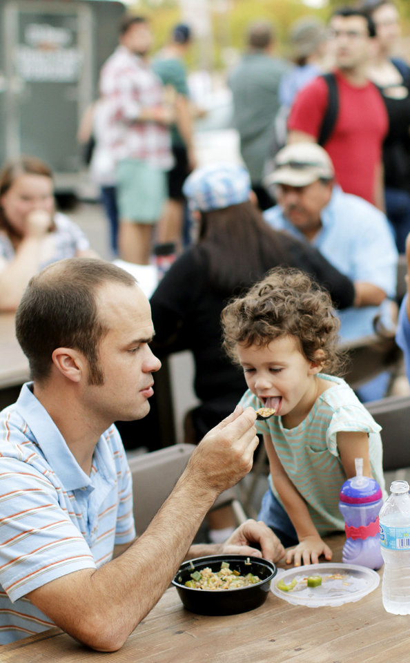 Photo - Cody Boswell shares his food with his daughter, Claire Boswell, 3, during H&8th on Hudson between 7th and 8th streets, Friday, September 27, 2013. Photo by Doug Hoke, The Oklahoman