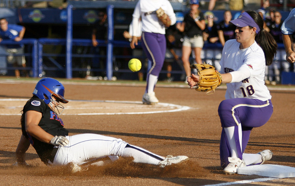 Photo - Florida's Aja Paculba slides to third as Washington's Morgan Stuart waits for the ball in the first inning of the second softball game of the championship series between Washington and Florida in Women's College World Series at ASA Hall of Fame Stadium in Oklahoma City, Tuesday, June 2, 2009. Photo by Bryan Terry, The Oklahoman