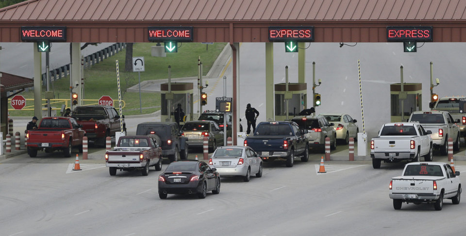 Photo - Security check vehicles as they enter Fort Hood's main gate, Thursday, April 3, 2014, in Fort Hood, Texas. A soldier opened fire Wednesday on fellow service members at the Fort Hood military base, killing three people and wounding 16 before committing suicide. (AP Photo/Eric Gay)