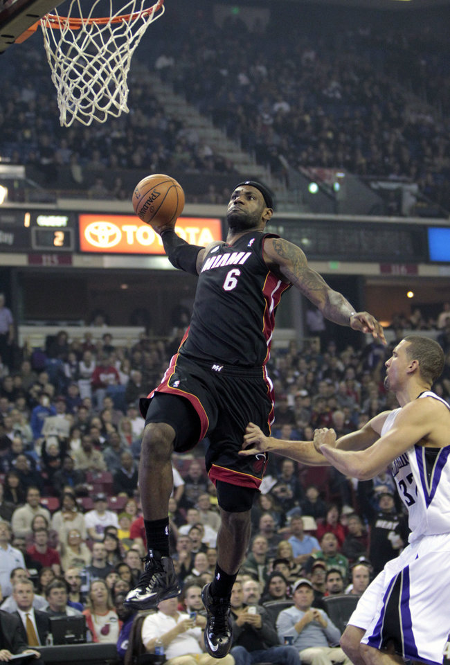 Photo - Miami Heat forward LeBron James, left, dunks over Sacramento Kings forward Francisco Garcia during the first quarter of an NBA basketball game in Sacramento, Calif., Saturday, Jan. 12, 2013. (AP Photo/Rich Pedroncelli)