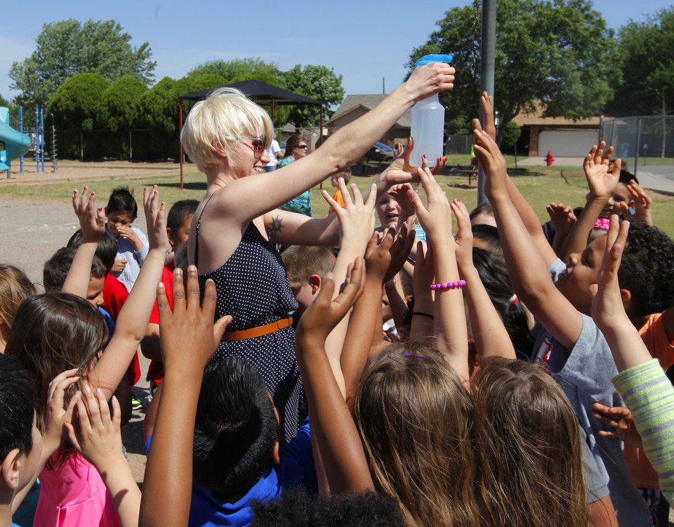 Photo -  Parent volunteer Cassie Poole sprays kids with a water bottle on the playground during a Cinco de Mayo celebration at Sunset Elementary School in Edmond. Photo by Paul B. Southerland, The Oklahoman   PAUL B. SOUTHERLAND -