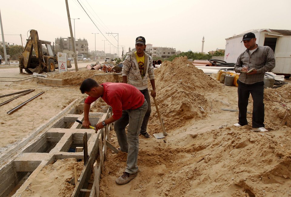 Photo - In this Monday, April 8, 2013 photo, Palestinians work on a Qatar-funded road in Gaza City. The newly re-elected leader of Hamas, Khaled Mashaal, is expected to strengthen ties with Qatar, Egypt and Turkey in his next four-year term. (AP Photo/ Hatem Moussa)
