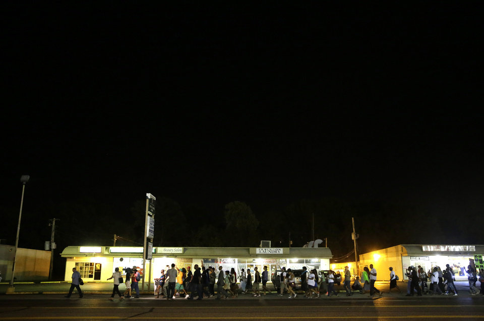 Photo - A line of protesters march into the evening Thursday, Aug. 21, 2014, in Ferguson, Mo. Protesters again gathered Thursday evening, walking in laps near the spot where Michael Brown was shot. Some were in organized groups, such as clergy members. More signs reflected calls by protesters to remove the white prosecutor from the case. (AP Photo/Jeff Roberson)