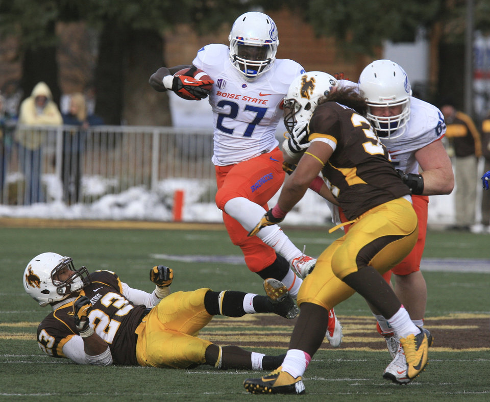 Photo -   Boise State's Jay Ajayi jumps over Wyoming's Ghaali Muhammad during an NCAA college football game Saturday, Oct. 27, 2012, at War Memorial Stadium in Laramie, Wyo. Boise State won 45-14. (AP Photo/Idaho Statesman, Chris Butler) LOCAL TV OUT (KTVB 7)