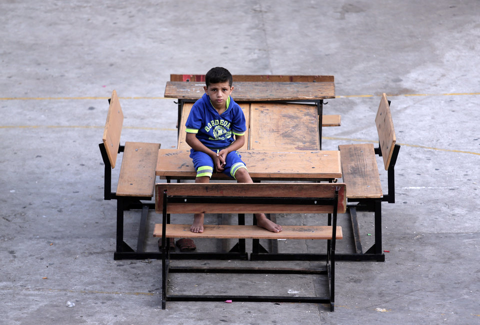 Photo - A Palestinian boy passes time in the courtyard of a U.N. school in Gaza City, Monday, July 28, 2014. Over 140,000 Palestinians are seeking shelter in 83 United Nations Relief and Works Agency schools, according to UNRWA spokesman Chris Gunness. The number of Palestinians seeking shelter since the ground operation began has increased seven-fold.(AP Photo/Lefteris Pitarakis)