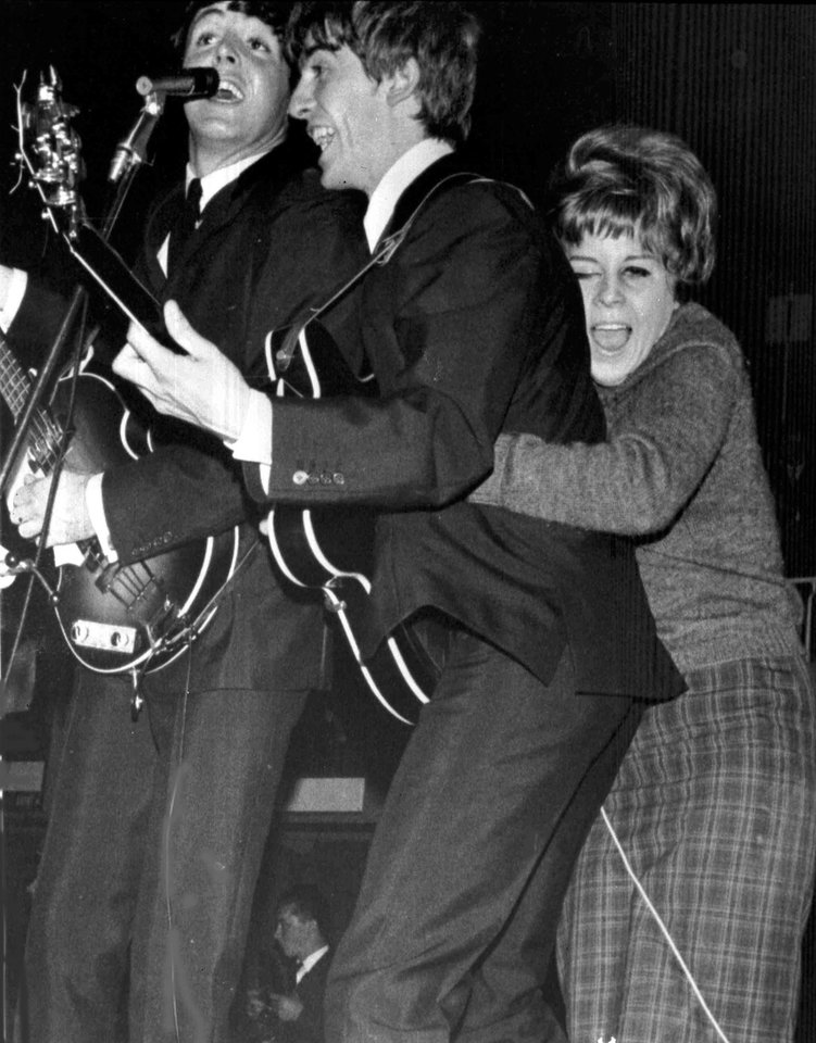 FILE - In this Oct. 26, 1963 file photo, a young fan hugs George Harrison as The Beatles play at a pop festival in Stockholm, Sweden. At left is Paul McCartney. (AP Photo/File)