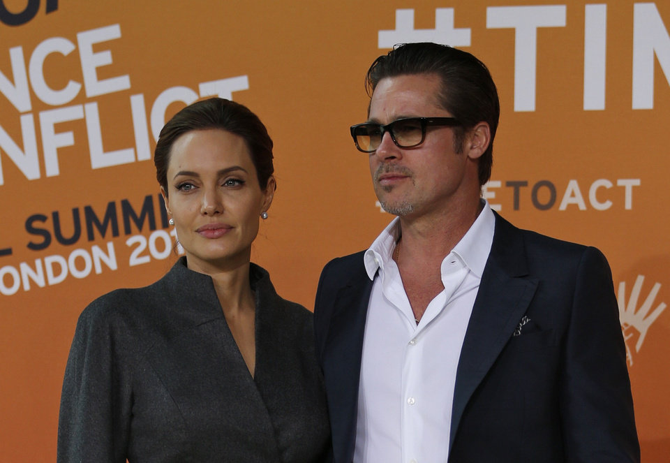 Photo - US actress Angelina Jolie, left, Special Envoy of the United Nations High Commissioner for Refugees, accompanied by her partner and US actor Brad Pitt pose for the photographers as they arrive at the 'End Sexual Violence in Conflict' summit in London, Friday, June 13, 2014. The Summit welcomes governments from over 100 countries, over 900 experts, NGOs, Faith leaders, and representatives from international organisations across the world. (AP Photo/Lefteris Pitarakis)