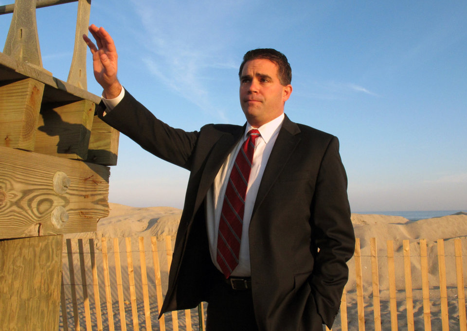 Photo - Belmar N.J. Mayor Matthew Doherty stands next to the lone 10-foot section of the 1.4-mile boardwalk in his Jersey shore community that survived Superstorm Sandy on Monday, Dec. 3, 2012. Belmar approved a $20 million spending plan Monday night to pay for a new boardwalk, as well as some of the cost of cleaning up the ruins of the old one. (AP Photo/Wayne Parry)