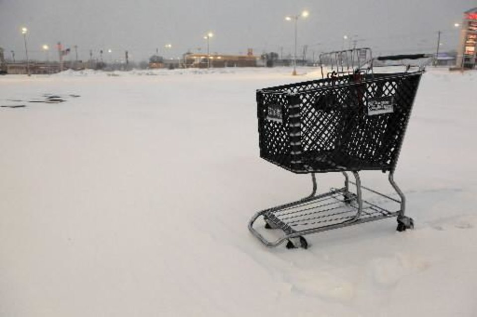 Photo - Shopping cart stuck in the snow in the middle of an empty parking lot at French Market Mall, NW 63 and May, in Oklahoma City Wednesday, Feb. 9, 2011. Photo by Paul B. Southerland