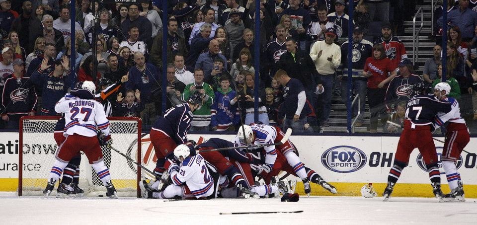 Photo - The Columbus Blue Jackets and New York Rangers fight during the second period of an NHL hockey game, Friday, March 21, 2014, in Columbus, Ohio. The scrum started when Rangers' Rick Nash pushed Blue Jackets goalie Sergei Bobrovsky. (AP Photo/Mike Munden)