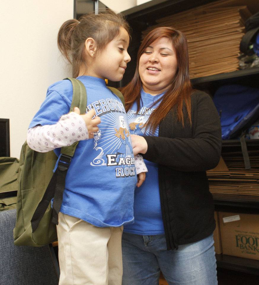 Erika Fierro gives a backpack from the Food for Kids Program to 4-year-old Ruby Alvarado on Friday at Heronville Elementary School in Oklahoma City. Photo By Paul Hellstern, The Oklahoman