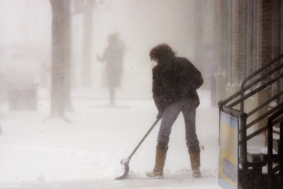 Photo - Michelle Bezpaletz shovels the sidewalk in front of her business, Forget-Me-Not Floral for the third time in two hours on Monday March 31, 2014 in Rapid City, S.D.  A spring snowstorm in the Upper Midwest on Monday shut down public schools, universities and government offices, made travel hazardous and life miserable for cattle ranchers in the midst of calving season. The National Weather Service issued blizzard warnings for much of the Dakotas and part of Minnesota, with the heaviest snow expected in eastern North Dakota and northwestern Minnesota.  (AP Photo/Rapid City Journal, Benjamin Brayfield)