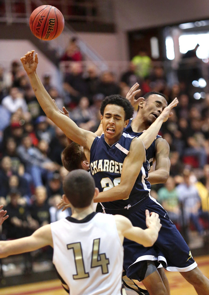 Photo - Heritage Hall's Calon Woods, #23, collides with Okemah player BenCustar (his head is under Woods' arm) while Heritage Hall's Chris Hamilton, back, and John Wingfield, #14, try to get possession of the loose ball during Class 3A boys basketball quarterfinal game between Okemah and Heritage Hall at Carl Albert High School on Thursday afternoon, Mar. 13, 2014. Photo by Jim Beckel, The Oklahoman
