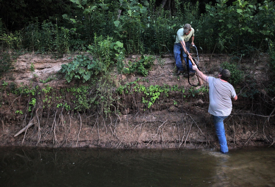 Johnny Heskett helps Josh Kinsey onto an embankment during a hunting trip near Indianola, Okla., Friday, July 6, 2012.  Photo by Garett Fisbeck, The Oklahoman