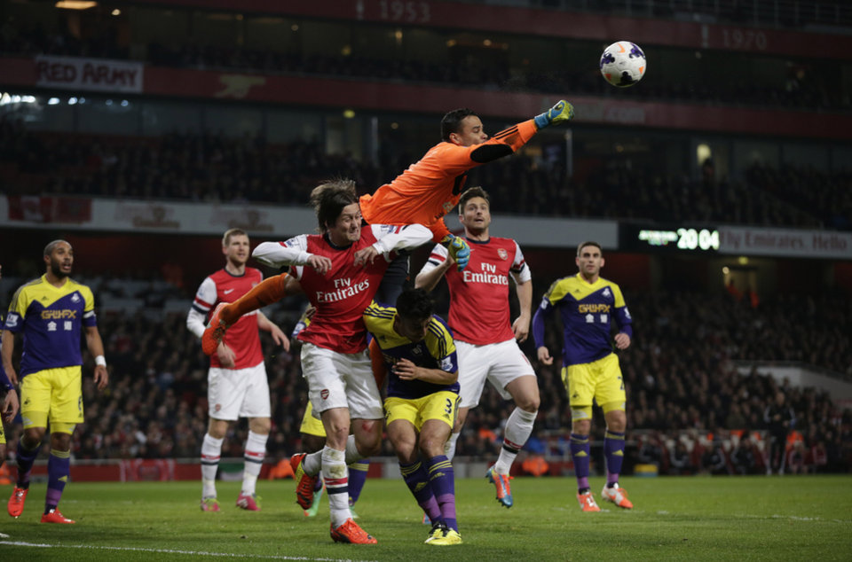 Photo - Swansea City's goalkeeper Michel Vorm punches the ball clear above Neil Taylor, 3, and Arsenal's Tomas Rosicky, center bottom left, during the English Premier League soccer match between Arsenal and Swansea City's at the Emirates Stadium in London, Tuesday, March 25, 2014. (AP Photo/Matt Dunham)