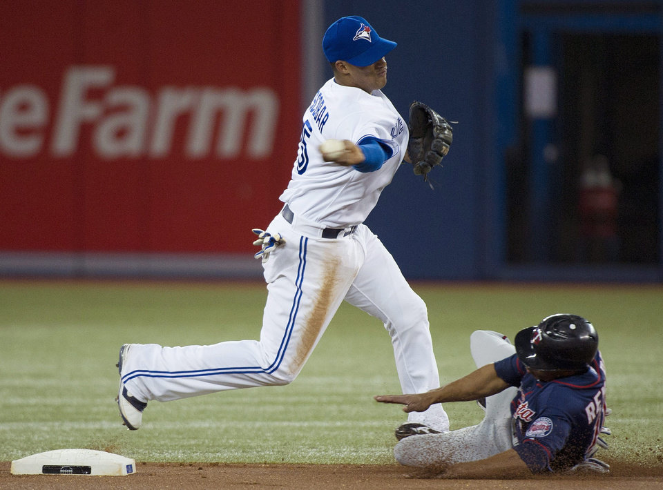 Photo -   Toronto Blue Jays shortstop Yunel Escobar, left, forces out Minnesota Twins right fielder Ben Revere while turning a double play during the first inning of a baseball game in Toronto on Tuesday, Oct. 2, 2012. (AP Photo/The Canadian Press, Nathan Denette)