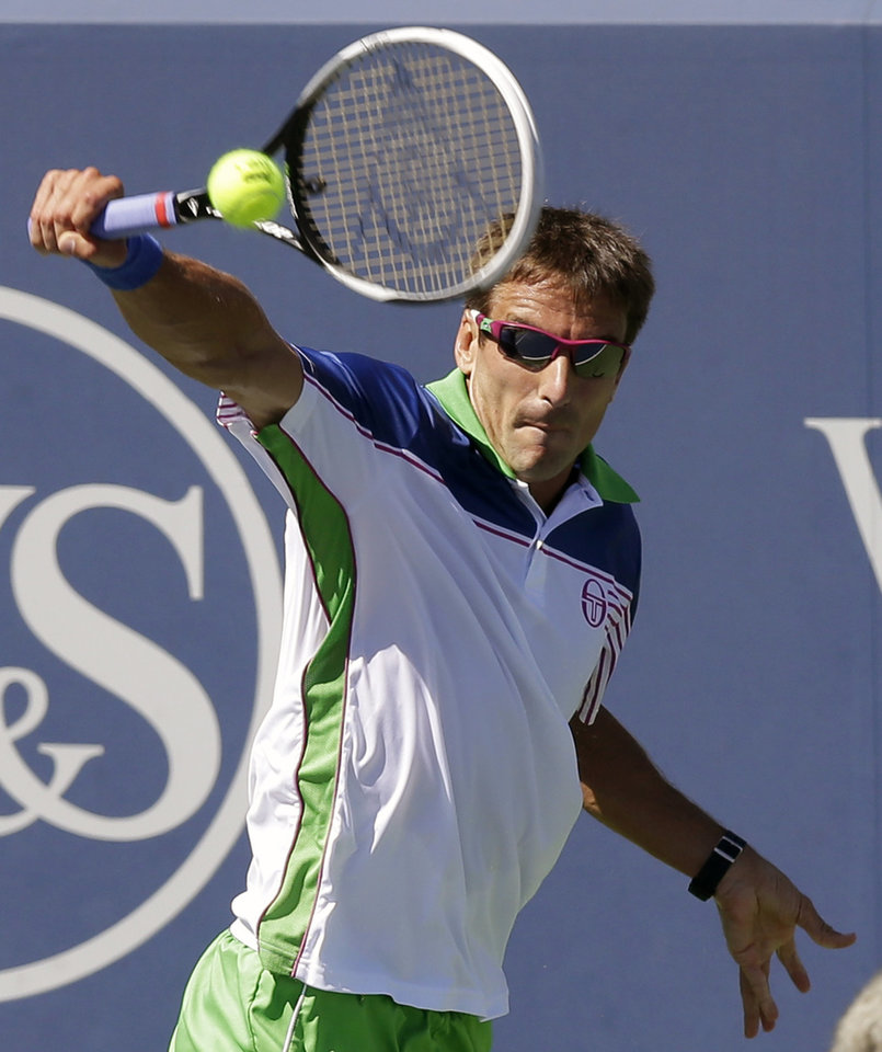 Photo - Tommy Robredo, from Spain, hits a backhand against David Ferrer, from Spain, during a match at the Western & Southern Open tennis tournament, Friday, Aug. 15, 2014, in Mason, Ohio. (AP Photo/Al Behrman)