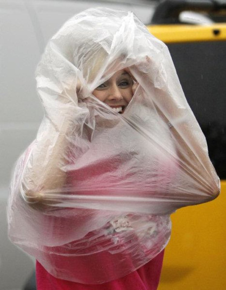 Photo - Lisa Scott, Oklahoma City, covers up as she helps her daughter Lindsey move into a dormitory at the University of Oklahoma as heavy rain falls on Thursday, August 11, 2011, in Norman, Okla.  Photo by Steve Sisney, The Oklahoman ORG XMIT: KOD