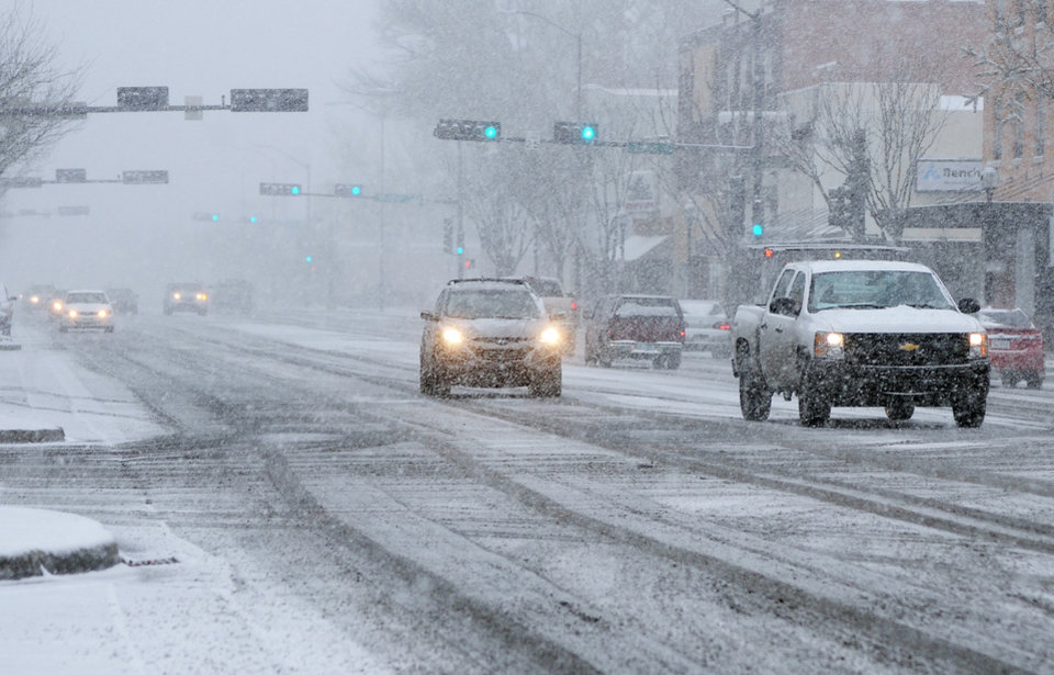 In this photo taken Thursday, Dec. 5, 2013, motorists proceed cautiously along Main Street as snow falls in downtown Roswell, N.M. (AP Photo/Roswell Daily Record, Mark Wilson)