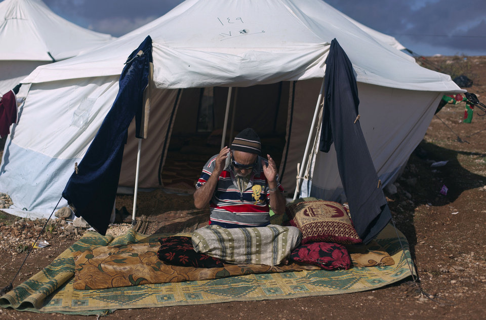 A Syrian elderly disabled man who fled from the violence in his village, prays in front of his tent at a displaced camp, in the Syrian village of Atma, near the Turkish border with Syria. Saturday, Nov. 10, 2012. (AP Photo/ Khalil Hamra)