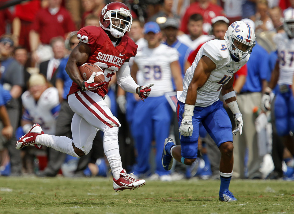 Photo - Oklahoma's Roy Finch (22) runs past Tulsa's Darnell Walker (4) during a college football game between the University of Oklahoma Sooners (OU) and the Tulsa Golden Hurricane at Gaylord Family-Oklahoma Memorial Stadium in Norman, Okla., on Saturday, Sept. 14, 2013. Oklahoma won 51-20. Photo by Bryan Terry, The Oklahoman