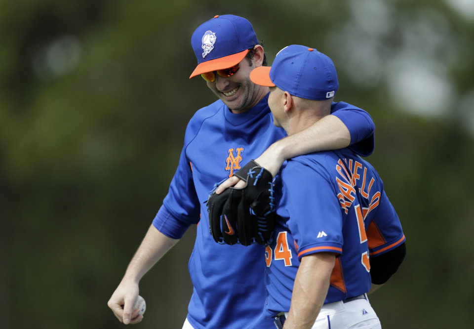 Photo - New York Mets pitcher Matt Harvey gets a gives a hug to bullpen catcher Dave Racaniello after the two played catch during spring training baseball practice Saturday, Feb. 22, 2014, in Port St. Lucie, Fla. Harvey underwent Tommy John surgery on Oct. 22. (AP Photo/Jeff Roberson)
