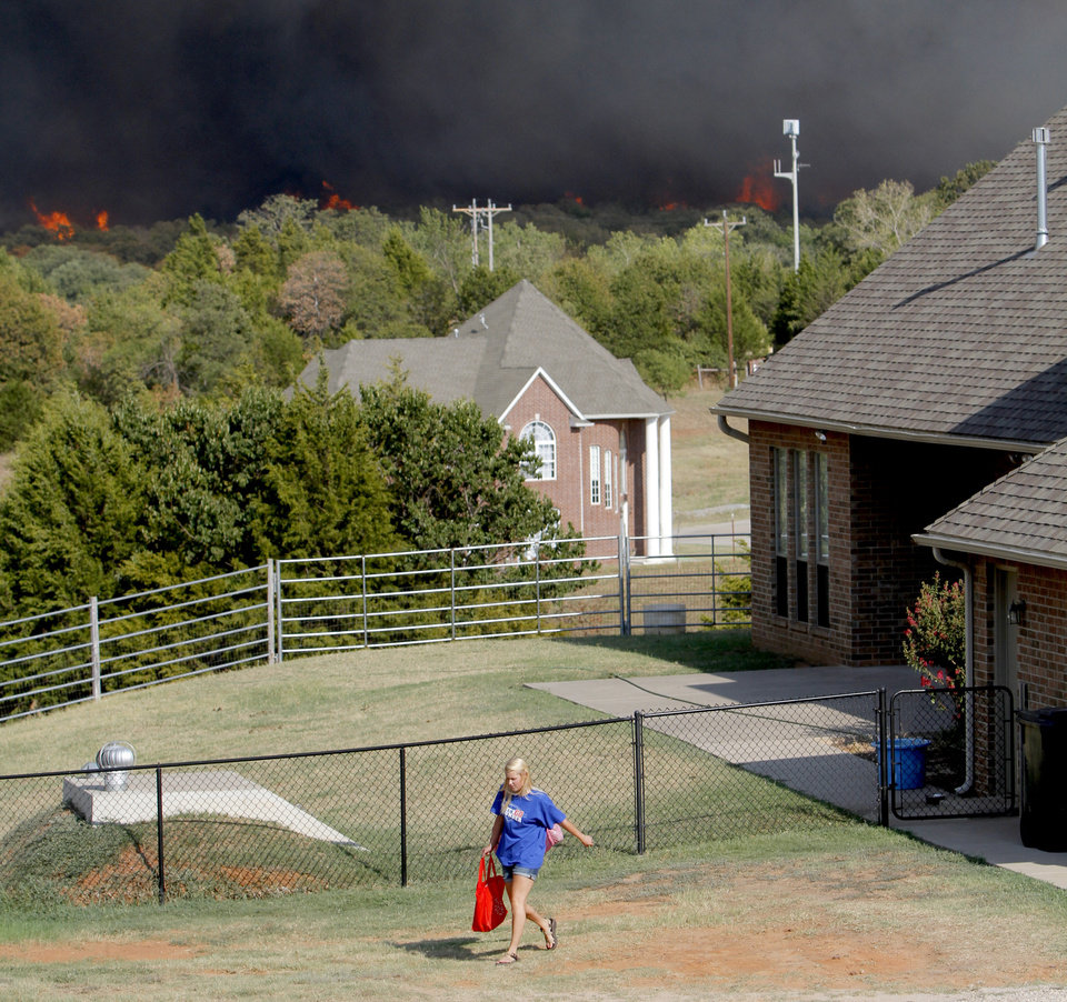 Photo - A resident leaves her house as flames from a wildfire approach near NW 122nd and Midwest Blvd. in Oklahoma City, Wednesday, August 31, 2011. Photo by Bryan Terry, The Oklahoman