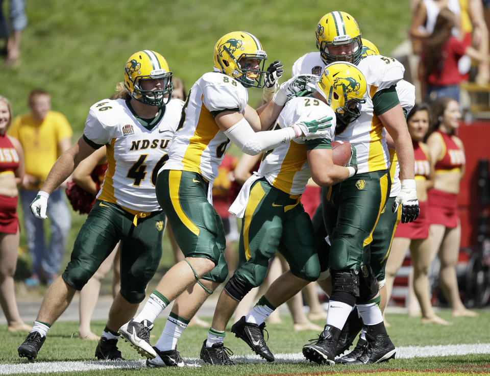 Photo - North Dakota State running back Chase Morlock (25) celebrates with teammates after scoring on a 66-yard touchdown run during the second half of an NCAA college football game against Iowa State, Saturday, Aug. 30, 2014, in Ames, Iowa. North Dakota State won 34-14. (AP Photo/Charlie Neibergall)