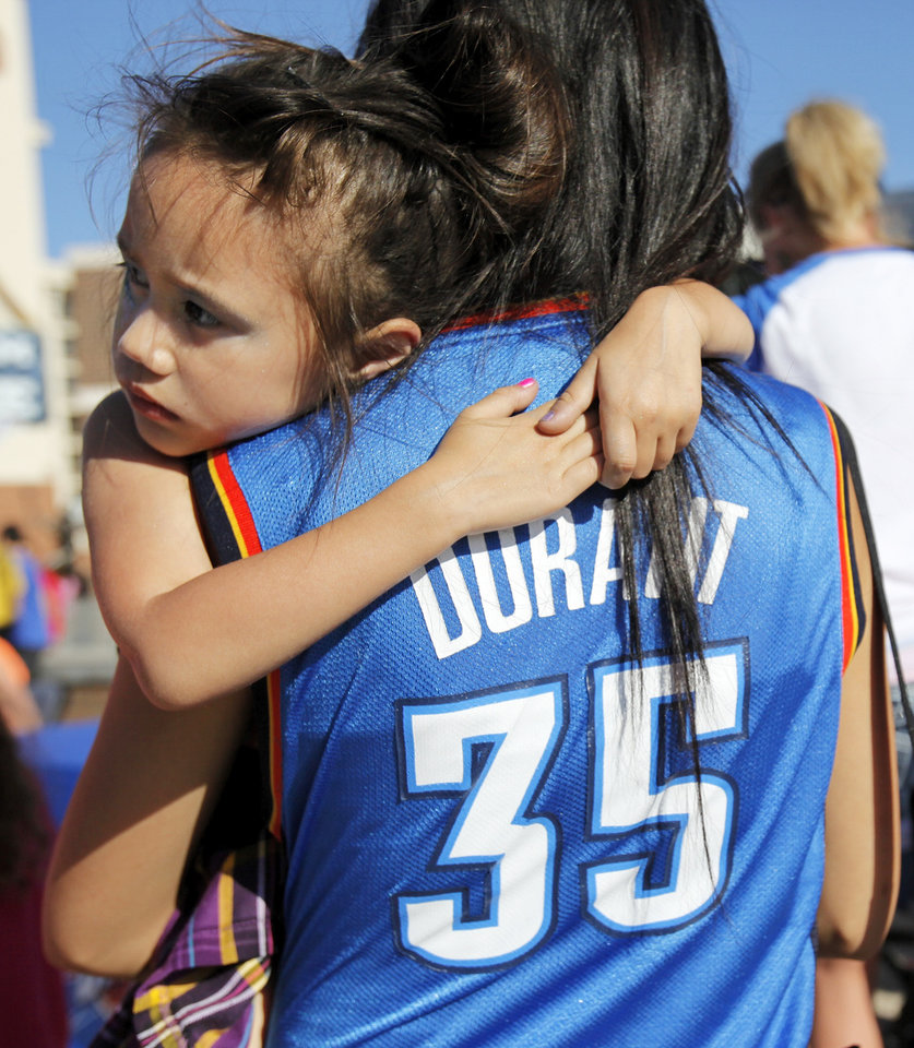 Photo - 3-year-old Mikenzi Bockhaus, of Oklahoma City, holds on to her mother, Jewlee Syharaj, in Thunder Alley before Game 4 of the Western Conference Finals between the Oklahoma City Thunder and the San Antonio Spurs in the NBA playoffs at the Chesapeake Energy Arena in Oklahoma City, Saturday, June 2, 2012.  Photo by Nate Billings, The Oklahoman