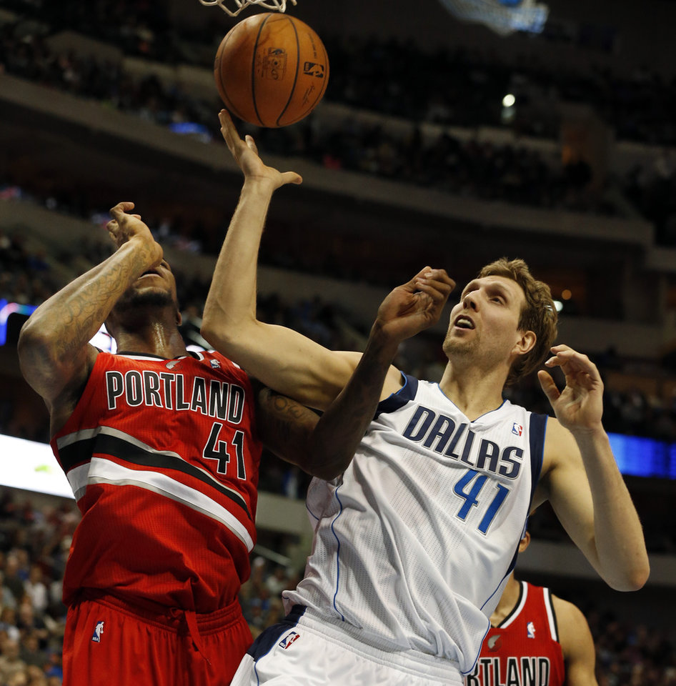 Photo - Portland Trail Blazers forward Thomas Robinson, left, and Dallas Mavericks forward Dirk Nowitzki, right, of Germany, fight for a loose ball during the first half of an NBA basketball game on Friday, March 7, 2014, in Dallas. (AP Photo/John F. Rhodes)