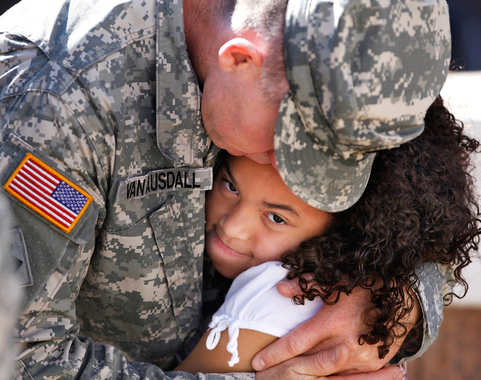 MILITARY DEPLOYMENT: SFC Joe Van Ausdall, Stillwater, OK, hugs Esmei Negron, 7,  of Ada, OK, the daughter of a fellow soldier as he says goodbye to his friend's family after the 45th Infantry Brigade Combat Team Deployment Ceremony in downtown Oklahoma City, Wednesday, Feb. 16, 2011. This will be Van Ausdall's third deployment.  Photo by Jim Beckel, The Oklahoman