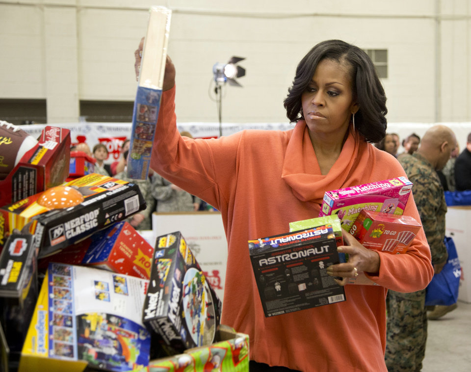 First lady Michelle Obama, puts some presents in a container as she helps sort out toys and gifts during her visit at the Joint Base Anacostia-Bolling to deliver toys and gifts to the Marine Corps\' Toys for Tots campaign in Washington, Tuesday, Dec. 11, 2012. (AP Photo/Manuel Balce Ceneta)