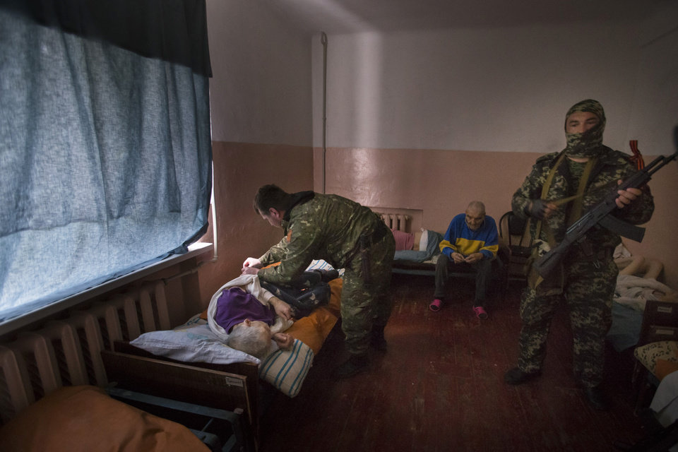 Photo - A pro-Russian armed militant assists a patient of a psychiatric hospital in Slovyansk, eastern Ukraine, on Sunday, May 25 2014. The hospital was badly damaged in an artillery shelling late Saturday and patients had to be evacuated. The rebels, who have fought government forces in the area in weeks of intense clashes, helped patients to get from the hospital's basement to a section that wasn't ruined by the shelling. (AP Photo/Alexander Zemlianichenko)