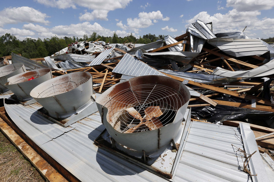 Photo - Ventilation fans sit on the ground behind the remains of the Hartness Farms, a 12-chicken house operation that was leveled in Noxapater, Miss., Wednesday, April 30, 2014. The farm was sold on Friday and its new owners were at the farm when a tornado demolished the property and injured them. There were no chickens at the farm.  (AP Photo/Rogelio V. Solis)