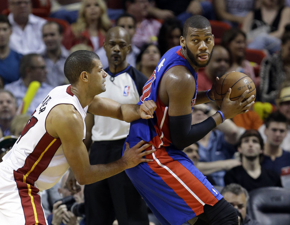 Photo - Detroit Pistons center Greg Monroe, right, drives up against Miami Heat forward Shane Battier during the first half of an NBA basketball game, Friday, Jan. 25, 2013 in Miami. (AP Photo/Wilfredo Lee)