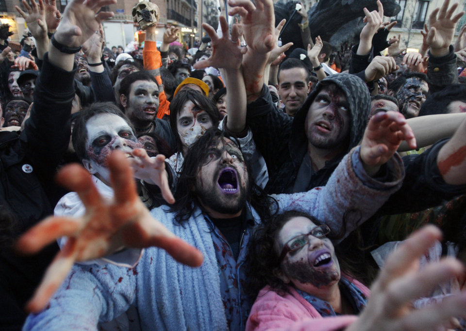 Photo - People dressed and made up as Zombies react, during the annual Zombie march, in Madrid, Saturday Feb. 27, 2010. The zombie  march is a homage to the Zombie film genre and to U.S. director George A. Romero, famous for his Zombie  horror movies. (AP Photo/Paul White)