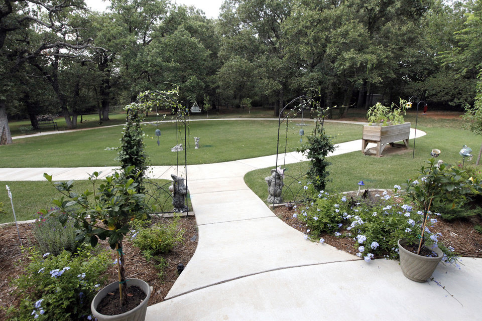 Photo - The garden, walking trail and backyard of a house in Logan County used as a non-traditional eldercare home. The flowers are a project of the resident of the house. PHOTO BY PAUL HELLSTERN, THE OKLAHOMAN.  PAUL HELLSTERN - THE OKLAHOMAN
