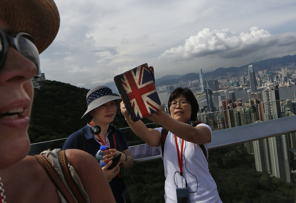 In this July 10, 2014 photo, tourists use a smart device to take photograph of themselves with the general view of Hong Kong at The Peak. Many in this prosperous city-state had already feared that Hong Kong's future as an open society as well as a semiautonomous part of China was in jeopardy in the face of growing intervention from Beijing. (AP Photo/Kin Cheung)