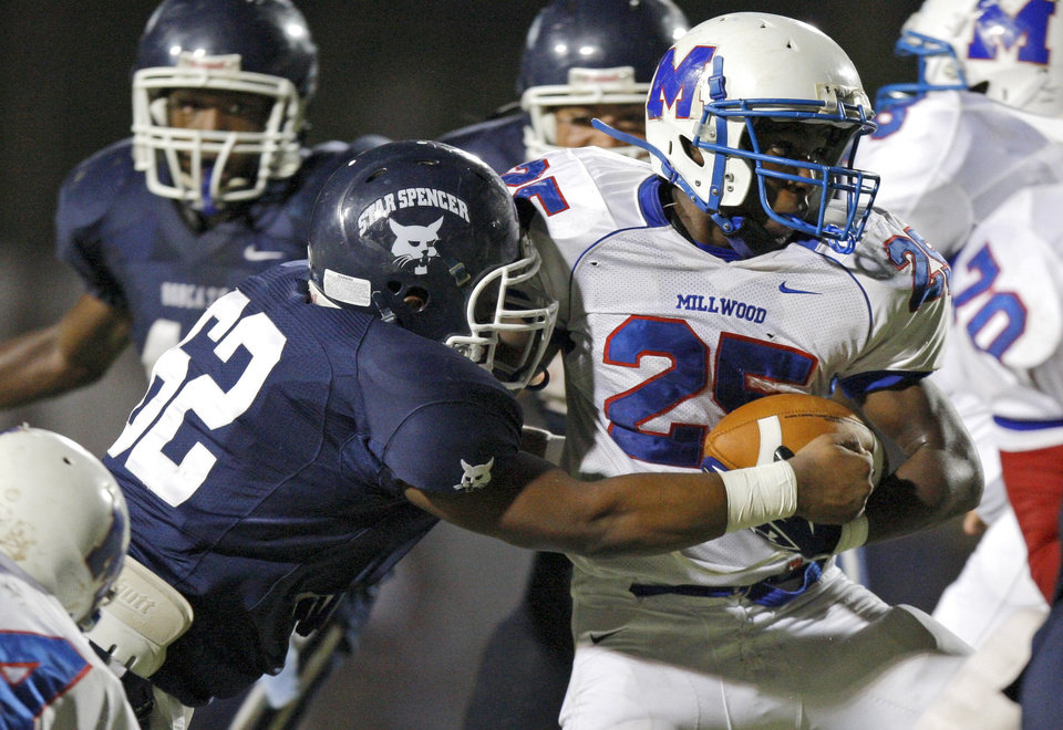 Photo - Millwood's Sheldon Bulock fights off Star Spencer's Shaun Hyche during a high school football game at Star Spencer in Oklahoma City, Friday, September 2, 2011. Photo by Bryan Terry, The Oklahoman