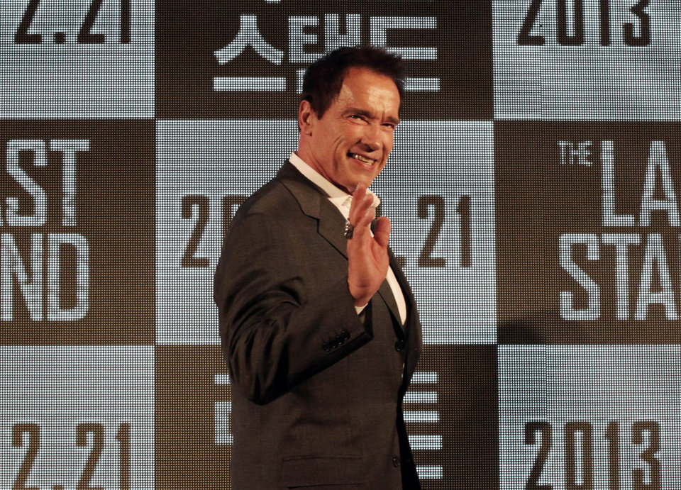 Photo - Actor Arnold Schwarzenegger waves as he arrives to hold a press conference to promote his latest film