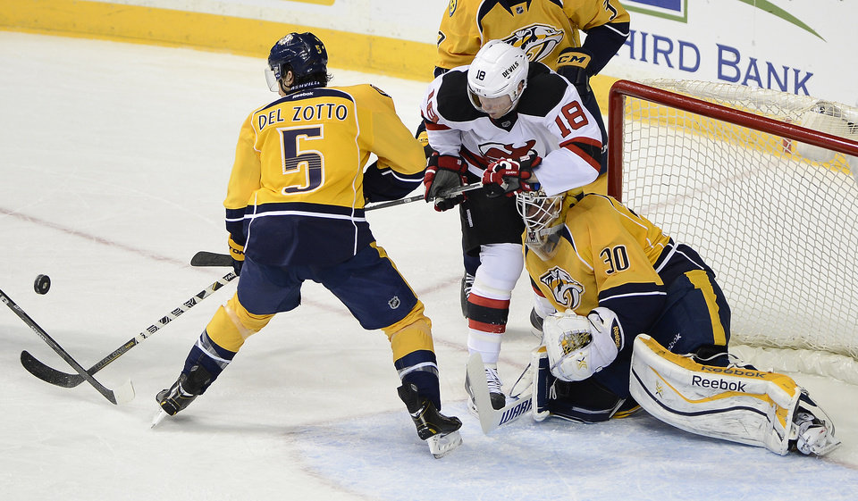 Photo - Nashville Predators defenseman Michael Del Zotto (5) and New Jersey Devils right wing Steve Bernier (18) battle for the loose puck in front of goalie Carter Hutton (30) in the second period of an NHL hockey game on Friday, Jan. 31, 2014, in Nashville, Tenn. (AP Photo/Mark Zaleski)
