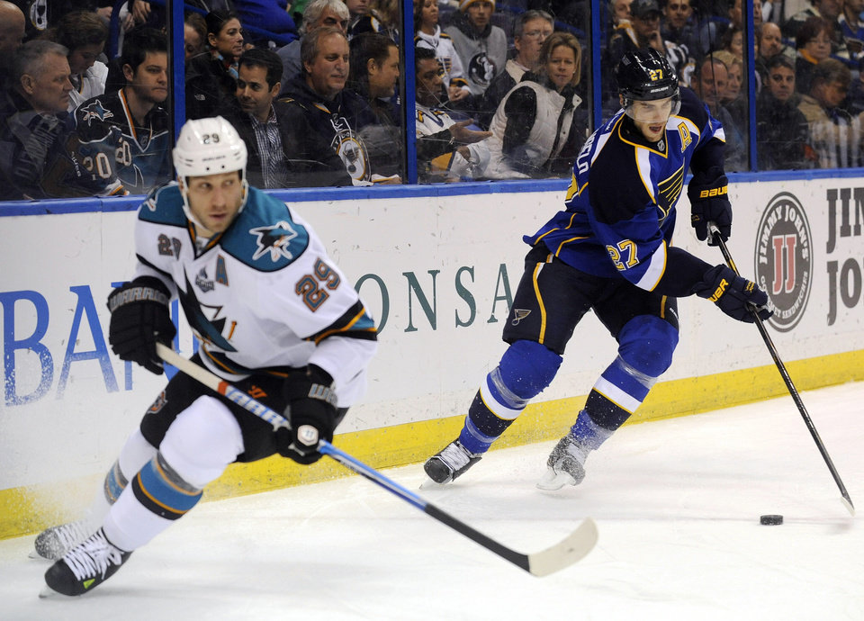 St. Louis Blues' Alex Pietrangelo (27) gets the puck behind San Jose Sharks' Ryane Clowe (29) in the first period of an NHL hockey game, Tuesday, Feb. 19, 2013, in St. Louis. (AP Photo/Bill Boyce)