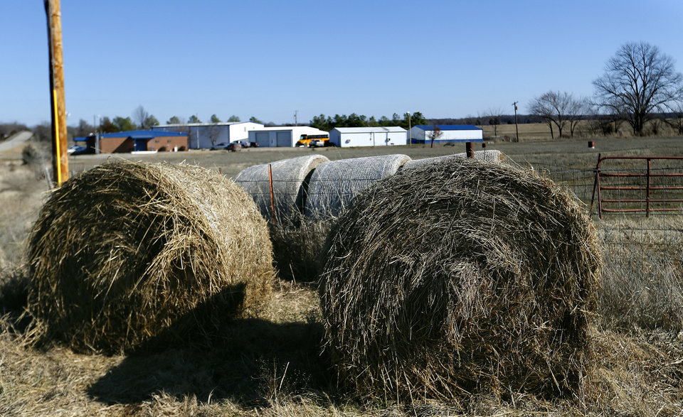 Photo - Hay bails are pictured in front of  Ryal Public School, Wednesday, Feb. 13, 2013. Photo by Sarah Phipps, The Oklahoman