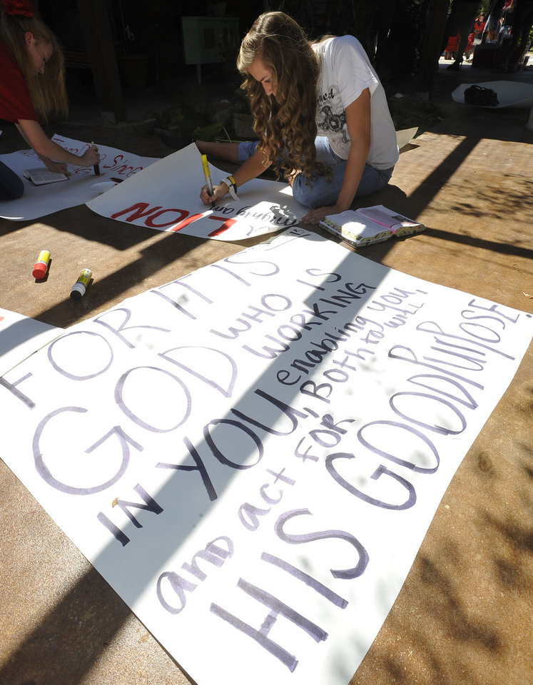 Photo -   Kountze High School cheerleader Grace Walton works on her sign next to a finished one Wednesday, Sept. 19, 2012 in Kountze, Texas. The small Hardin County community is rallying behind the high school's cheerleaders after the squad members were told they could not use scripture verses on their signs at the football games. (AP Photo/The Beaumont Enterprise, Dave Ryan)