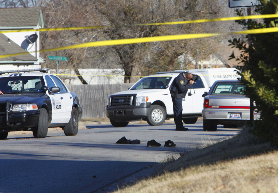 Photo - A law enforcement officer takes photographs Tuesday at the scene of a police officer-involved shooting at the corner of Cashion Place and N Youngs Boulevard in Oklahoma City. In the road are the shoes and clothing of the deceased suspect. Photo By David McDaniel, The Oklahoman